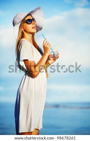 Woman having rest on beach and enjoying a fresh cocktail summer - stock photo