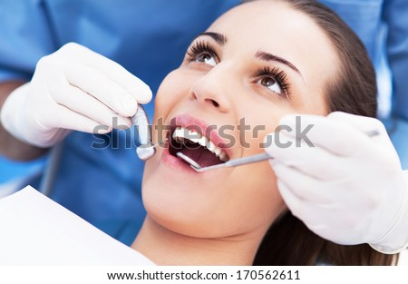 Woman having teeth examined at dentists - stock photo