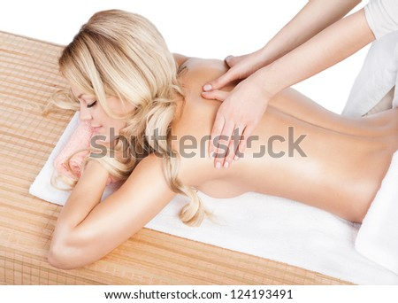 Woman having therapy massage of back in the spa salon. Beauty treatment concept. Blonde woman relaxing with hand massage at beauty spa. Shoulder massage. Horizontal. Studio shot. White background.