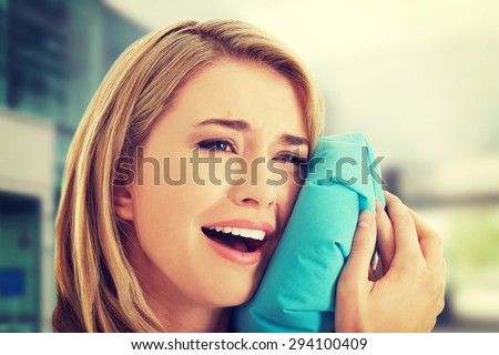 Woman having tooth ache holding ice bag near face - stock photo