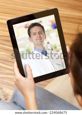 Woman having video chat with doctor on laptop at home - stock photo