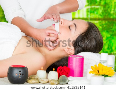 Woman headshot profile, lying with eyes closed and hand applying wax paper to upper lip of client