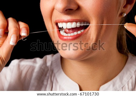 Woman healthy teeth closeup with toothbrush on black background - stock photo