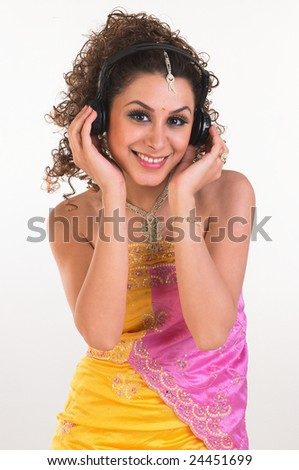Woman hearing headphones with pink and yellow sari