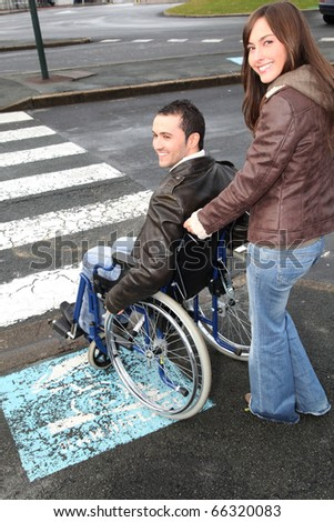 Woman helping friend in wheelchair cross the street - stock photo