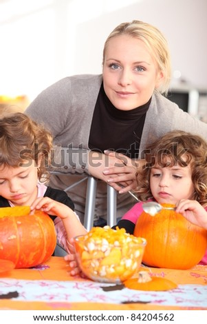 Woman helping her children carve pumpkins - stock photo