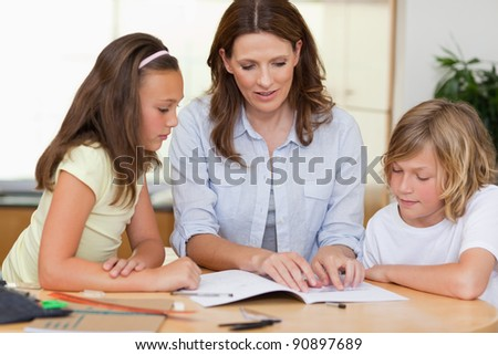 Woman helping her children with homework - stock photo