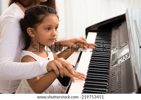 Woman helping her daughter to play the piano, body and buttons of the piano were digitally modified - stock photo