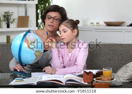 Woman helping her granddaughter complete her geography homework - stock photo