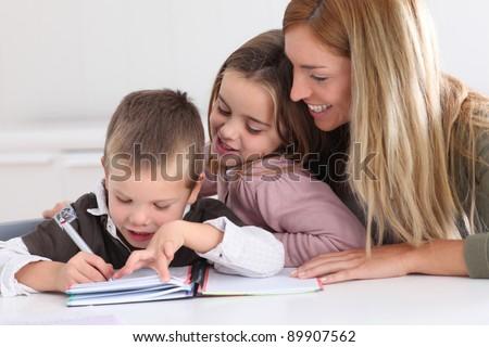 Woman helping kids with homework - stock photo