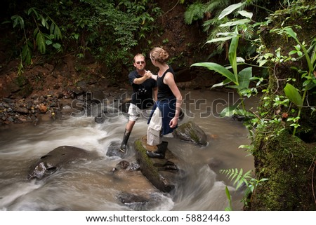 Woman helping man cross ruching Costa Rican river - stock photo