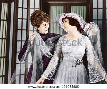 Woman helping younger woman dress - stock photo