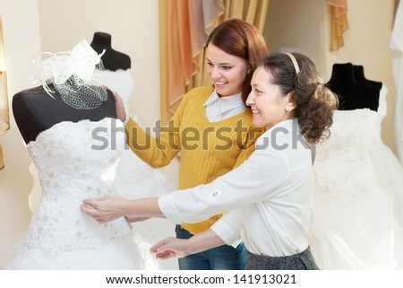 woman helps the gitl choosing bridal gown at shop of wedding fashion. Focus on mature - stock photo