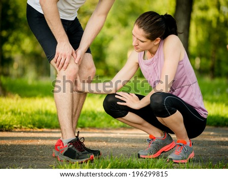 Woman helps to man with injured knee at sport activity - stock photo