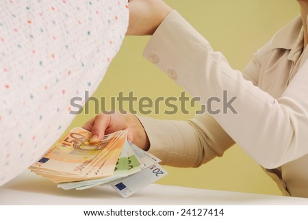 Woman hides money under pillow - stock photo