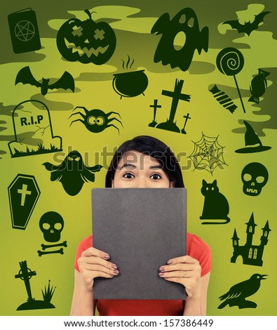 woman hiding behind a book with halloween background - stock photo