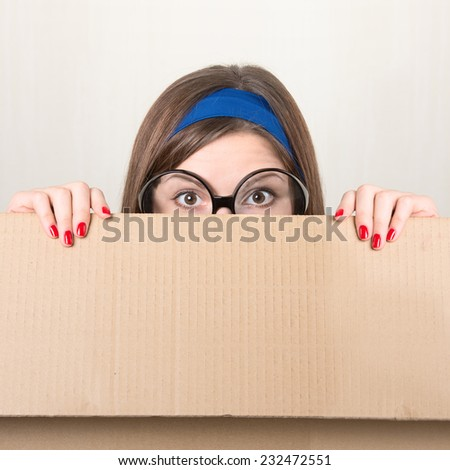 Woman hiding behind a moving box - stock photo
