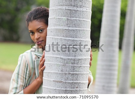 Woman hiding behind a tree - stock photo