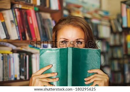Woman hiding behind the green book - stock photo