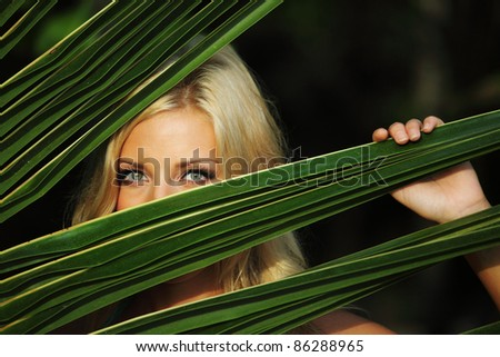 woman hiding behind the palm leaves - stock photo