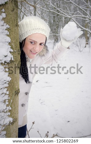 woman hiding behind tree throwing snowball in snow covered forest - stock photo