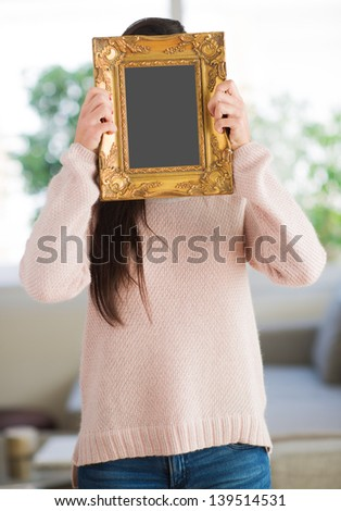 Woman Hiding Face With Picture Frame, Indoors