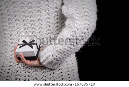 woman hiding gift box behind her back - stock photo