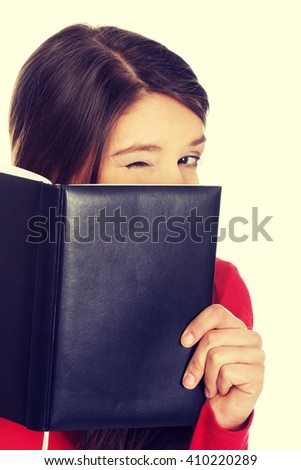 Woman hiding her face behind a notebook.