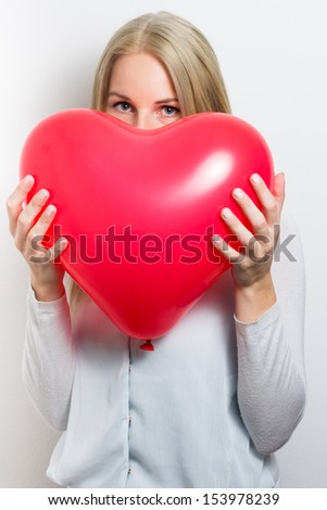 Woman hiding her face behind a red heart