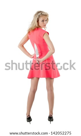 woman hiding knife behind her back and looking back over her shoulder - stock photo