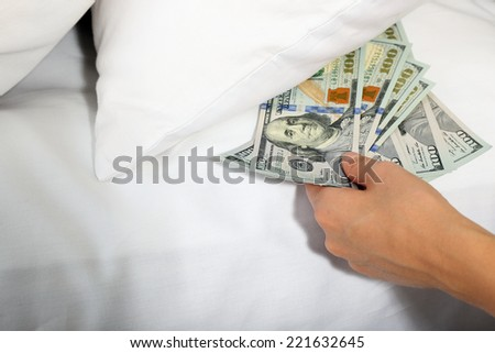 Woman hiding money under pillow at home - stock photo