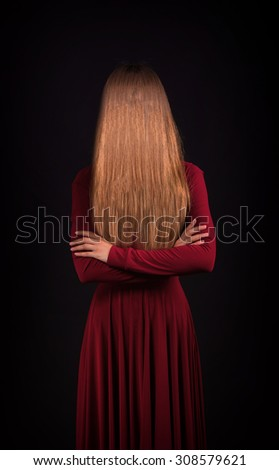 Woman hiding the face behind her long hair, dark background  - stock photo