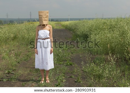 woman hiding under empty paper bag over summer background - stock photo