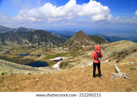 Woman hiker admires the mountain landscape in sunny summer day - stock photo