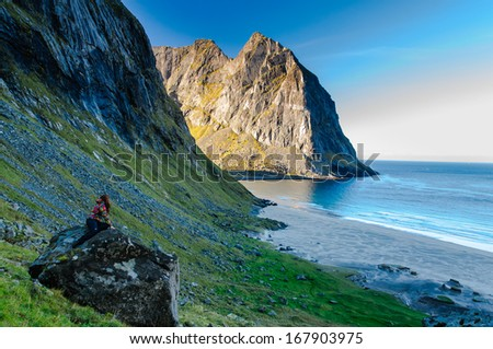 Woman hiker amazed by the view at famous Kvalvika beach hidden between steep cliffs of Lofoten mountains, Norway - stock photo