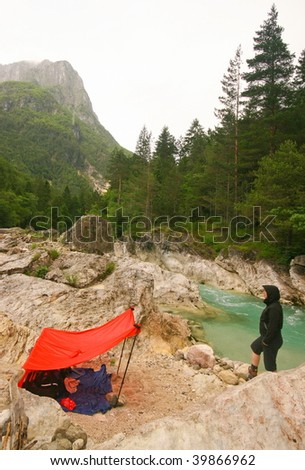 Woman hiker and rain shelter in mountains with river - stock photo