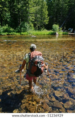 woman hiker crossing the Popo Agie River in Wyoming's Wind River Range - stock photo