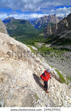 Woman hiker descending on steep section of the Durissini trail, Cadini di Misurina, Dolomite Alps, Italy - stock photo