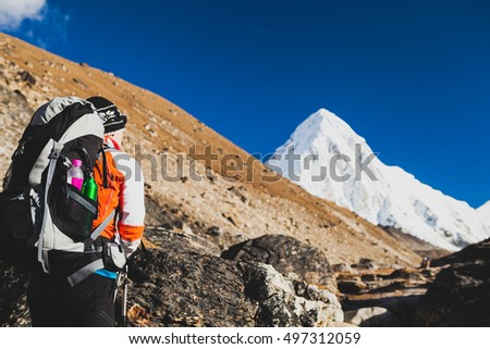 Woman Hiker Hiking in Himalaya Mountains in Nepal. Trekking with backpack in Himalayas to Everest Base Camp. Travel, Exploration and Fitness Concept. Sunny Day with Pumori Summit in Background.