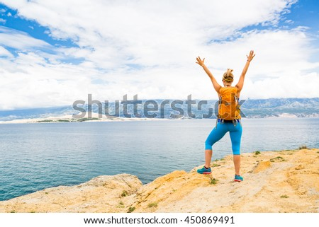 Woman hiker hiking with backpack, arms outstretched looking at sea and mountains view. Accomplished climber with hands up outdoors. Beautiful inspirational landscape. Trekking and activity concept. - stock photo