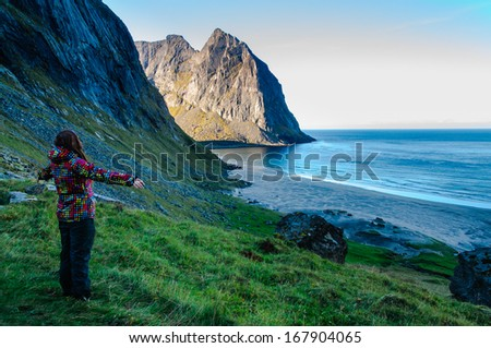 Woman hiker in colorful jacket amazed by the view at famous Kvalvika beach hidden between steep cliffs of Lofoten mountains, Norway - stock photo