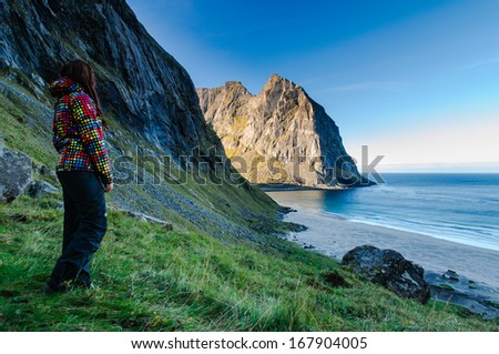 Woman hiker in colorful jacket enjoys the view at famous Kvalvika beach hidden between steep cliffs of Lofoten mountains, Norway - stock photo
