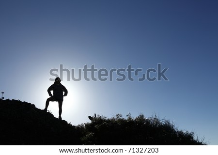 Woman hiker in silhouette standing on top mountain - stock photo