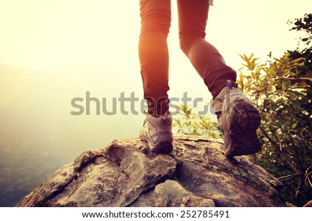 woman hiker legs on mountain peak rock  - stock photo