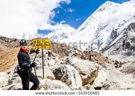 Woman hiker nordic walking on footpath in Himalaya Mountains in Nepal. Trekking on rocky footpath in autumn nature, beautiful mountain landscape. - stock photo