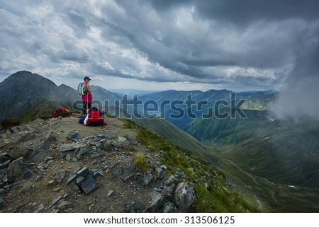 Woman hiker on a trail in the mountains in a beautiful scenery - stock photo