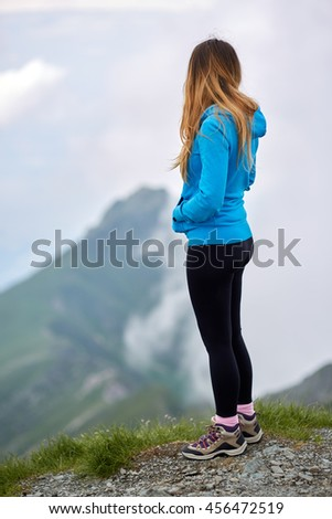 Woman hiker on top of the mountain admiring the view - stock photo