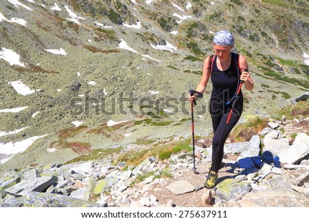 Woman hiker pushing up the mountain in sunny summer day - stock photo