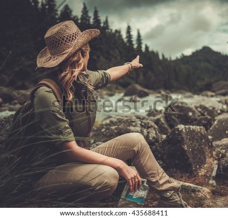 Woman hiker, searching right direction on map near wild mountain river. - stock photo