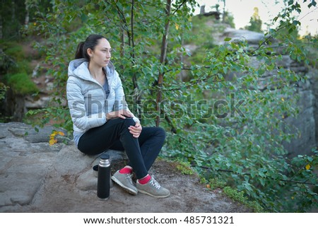 woman hiker sitting on a big stone  top of the mountain with thermos and cup  tea near her